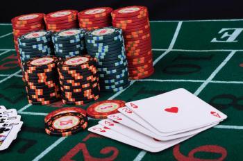 Högar med spelmarker i olika färger och spelkort med ess, två, tre, fyra och fem i hjärter på ett spelbord.